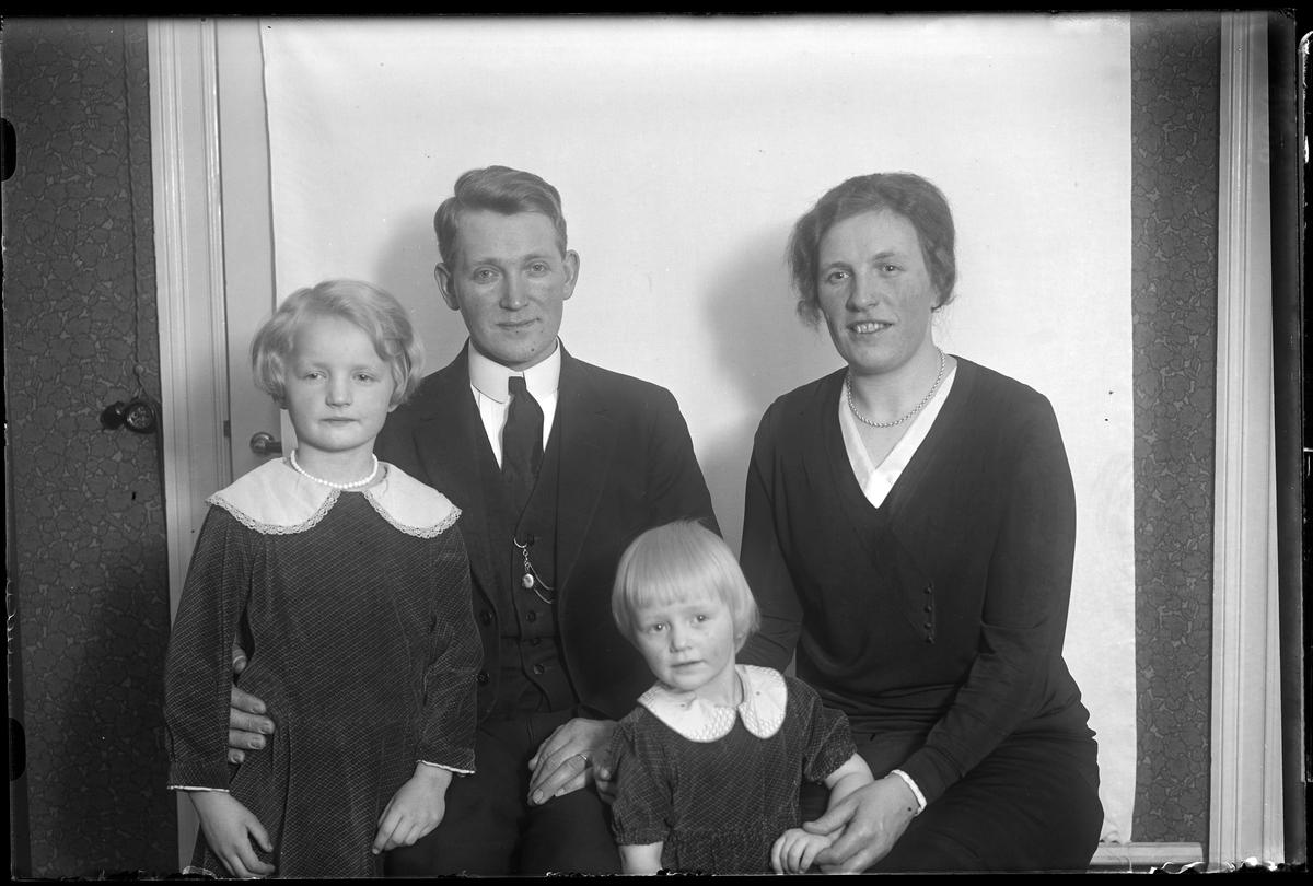 """Familjeporträtt på en kvinna och en man samt två barn. Familjen sitter vid en vit bakgrund och föräldrarna håller om varsin dotter. I fotografens egna anteckningar står det """"Carl Dahlén med familj""""."""