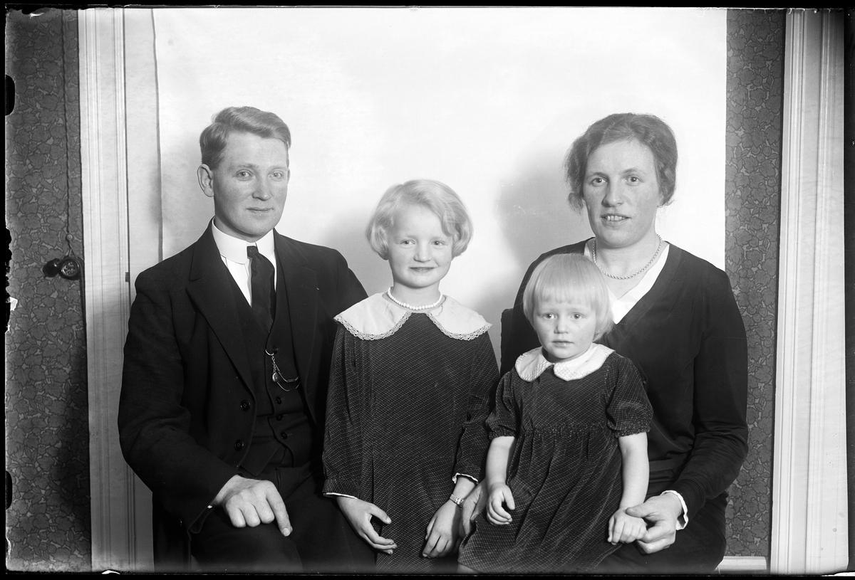 """Familjeporträtt på en kvinna och en man samt två barn. Familjen sitter framför en vit bakgrund och alla bär mörka kläder. I fotografens egna anteckningar står det """"Carl Dahlén med familj""""."""