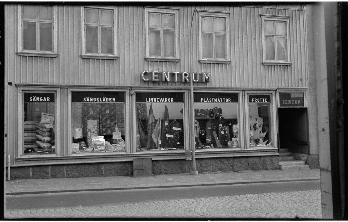 Firma Centrum. Norra Strömgatan 7, kvarteret Färgaren 3.  Butiksexteriör tagen rakt framifrån.  Huset av trä med lockpanel.  Låg stenfot och trappa till butiken infälld i fasaden. Fem fönster syns på våningen ovanför butiken. Butiken har fem stora skyltfönster som täcker hela fasaden, dessa fönster är inte original utan upptagna när det blev butik i bottenplan.  Butikens namn CENTRUM sitter direkt på fasaden, neonbokstäver. I skylfönstern sitter skyltar i överkant med texterna SÄNGAR SÄNGKLÄDER LINNEVAROR PLATMATTOR FROTTÉ Ovanför trappan står det CENTER.  Trottoaren är belaggd med stenplattor och gatan är stensatt med gatsten.