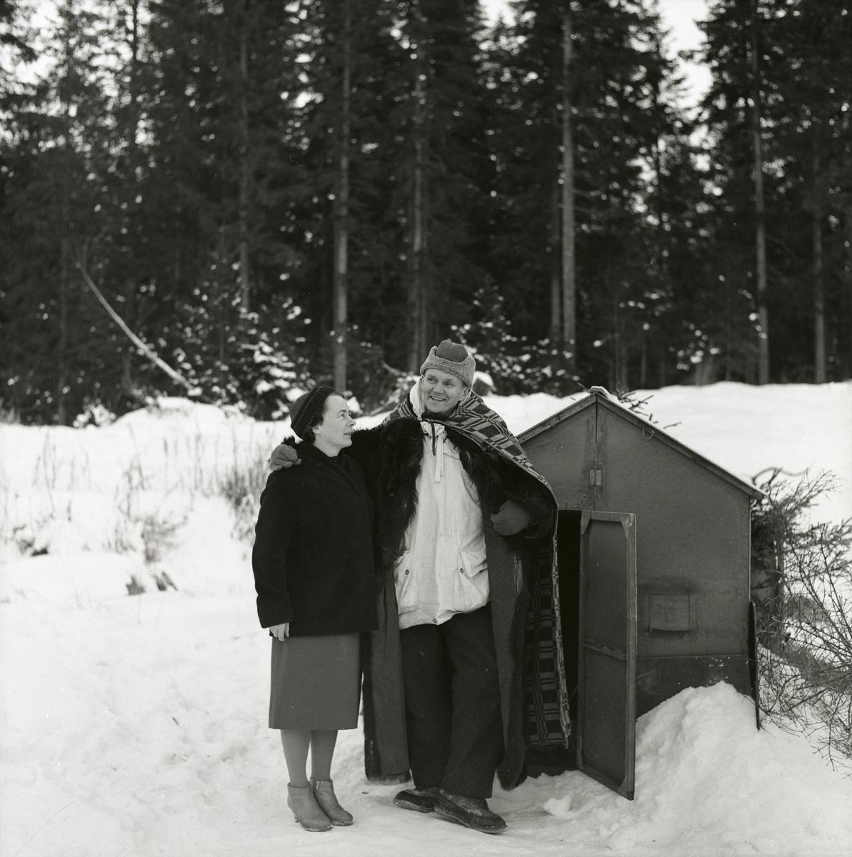 Adéle och Hilding framför öppningen till en koja i skogen. Det är snö och Hilding har ett täcke över axlarna, 1962.