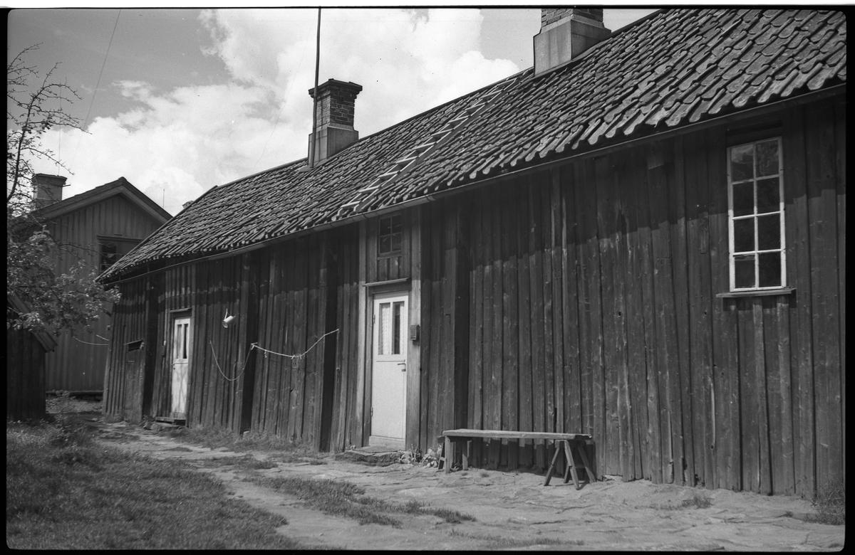 Gårdsinteriör från Drottninggatan 35, kv Jägaren. Ett boningshus av trä skymtar med gaveln åt fotografen. En låg uthusbyggnad av trä dominerar bilden.  Byggnaden är enplans med sadeltak och två skorstenar. Kan någon haft sin bostad där? Utanför en av dörrarna sitter en postlåda av plåt. Gardiner i dörrens fönster.  Två dörrar med fönster i båda, även stycket ovan dörrarna är fönster. Dörrarna tycks modernare än själva byggnaden. En kalkstensplatta som trappsteg.  Till höger, långt från dörrarna, sitter ett fönster med 2x4 smårutor.  Till höger om en av dörrarna står en enkel bänk, benbockar och en sittyta  Mellan dörrarna, längs väggen, är en tvättlina spänd, några klykor fastklämda.  Marken framför är upptrampad gräsmatta utan beläggning.  På taket ligger en stege som når fram till ena skorstenen.
