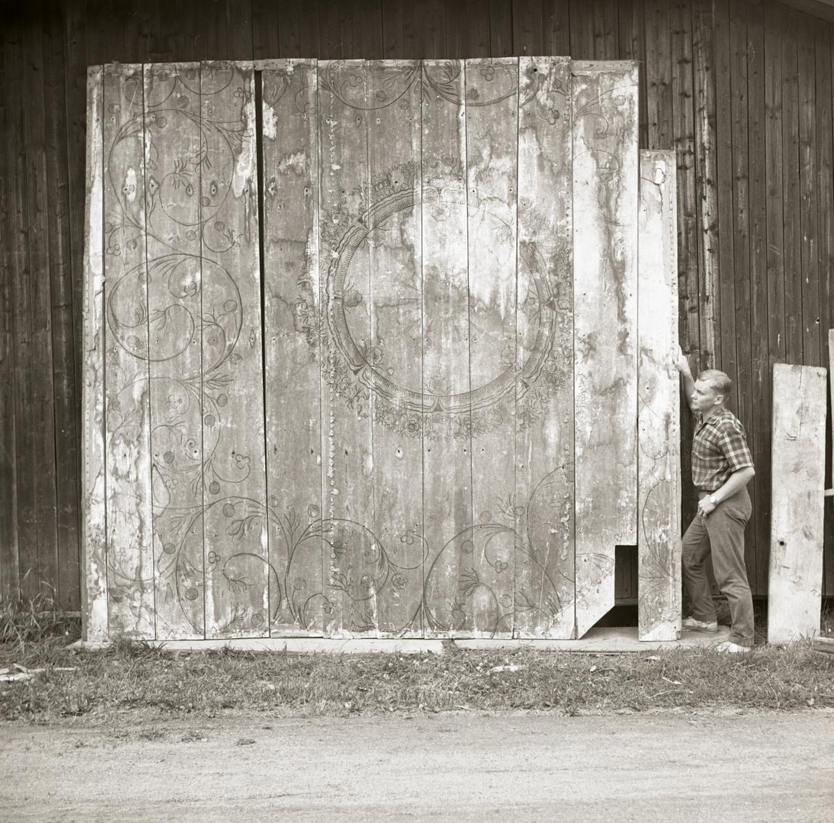 En man står bredvid målade innertaksbrädor vilka är lutade mot en vägg, 1968-1969.