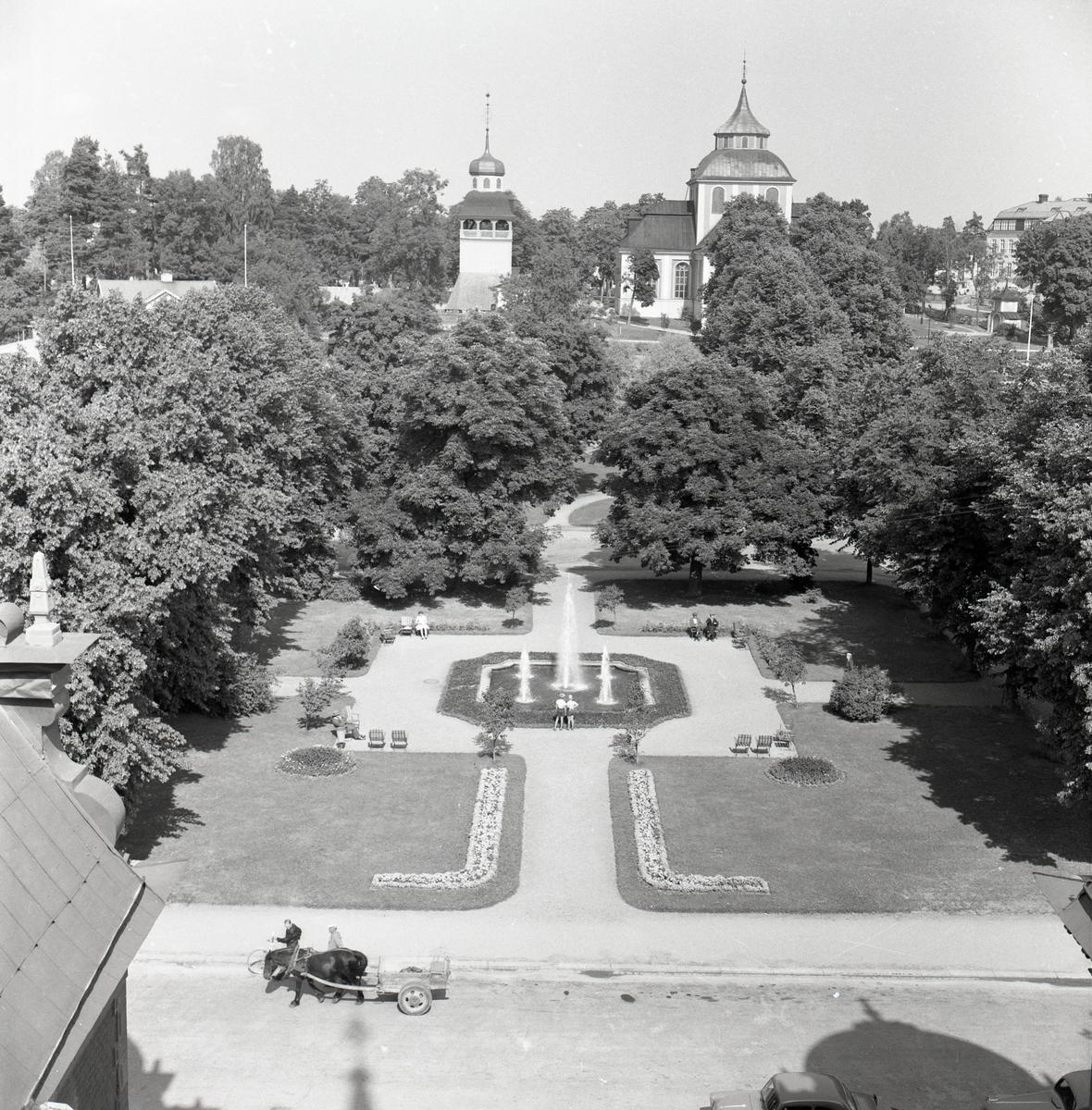 Vy från Söderhamns rådhus över parken med Ulrika Eleonora kyrka i bakgrunden. På gatan nedanför passerar en häst med vagn, 1955.
