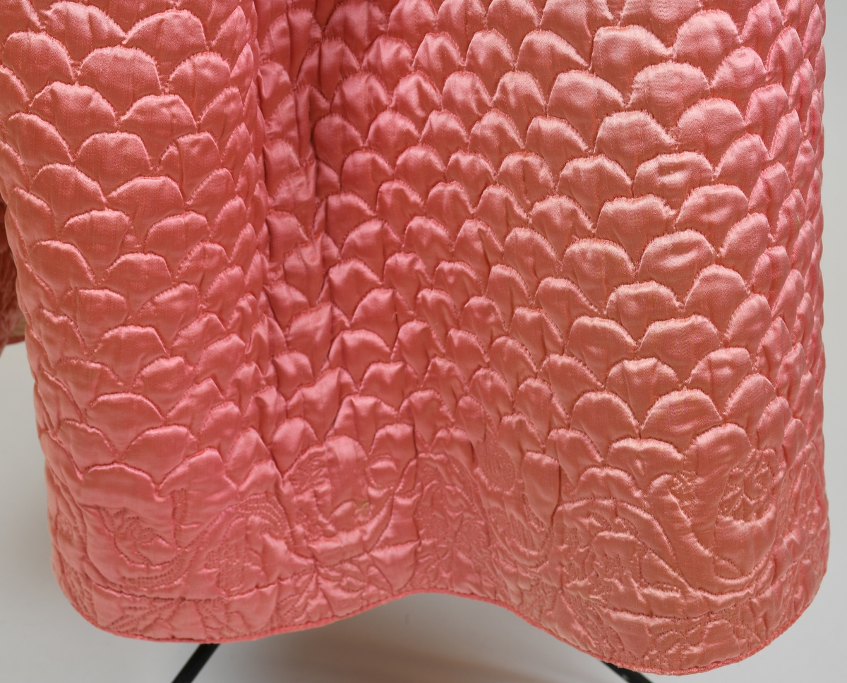 """Anmärkningar: Underkjol. Troligen brudunderkjol """"stubbe"""" av rosa sidensatin. Vågformade prickstickningar över hela bak- och framvåden, nederkanten med bred blombård. Veckat mot linning av fodertyget. Sprund i sidorna som knyts ihop med rosa sidenband, sprunden och nederkanten kantat med rosa sidenband av annan kvalitet. Fodrat med rosa bomullslärft. Vadderat. blekt, fläckigt. Vidd 274 cm."""