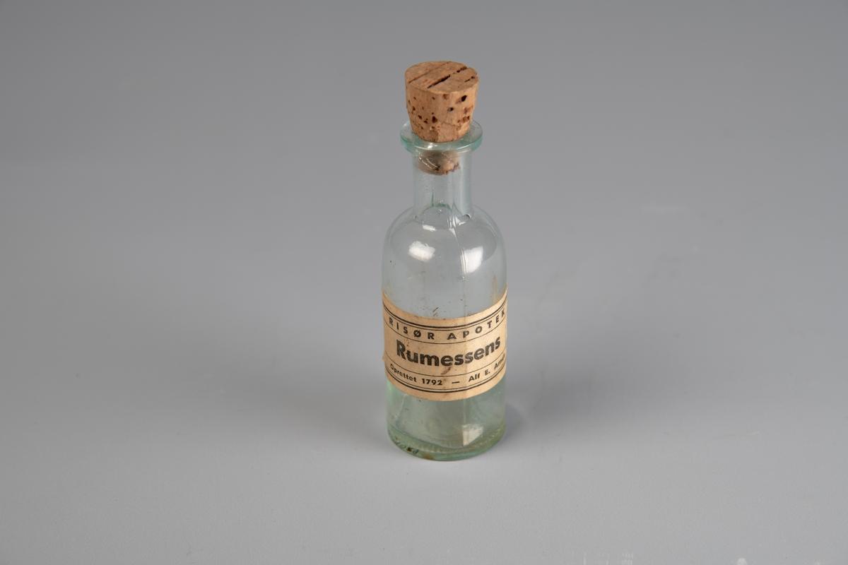 Rett flaske med hals og utkraget munning. Korken sitter fremdeles i. Pålimt etikett der det står at flasken inneholder romessens. Innstøpt ml-mål langs flasken. 30 (for 30 ml) støpt i bunnen.  Romessens er et aromastoff, som brukes som erstatning for ekte rom i desserter, kaker og slikt. Opprinnelig ble essensen fremstilt av ekte rom, men i moderne tid lages smaken av andre ingredienser.