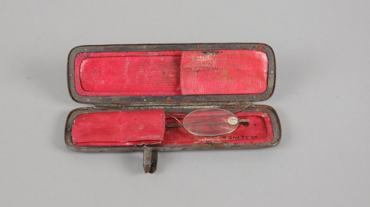 Brilleetui av skinn og metallramme med rødt fór. I etuiet ligger det ett par briller.