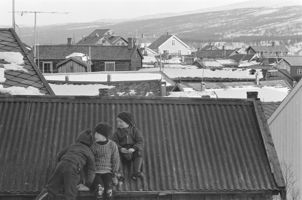 Barn leker i et snødekt bylandskap på Røros.