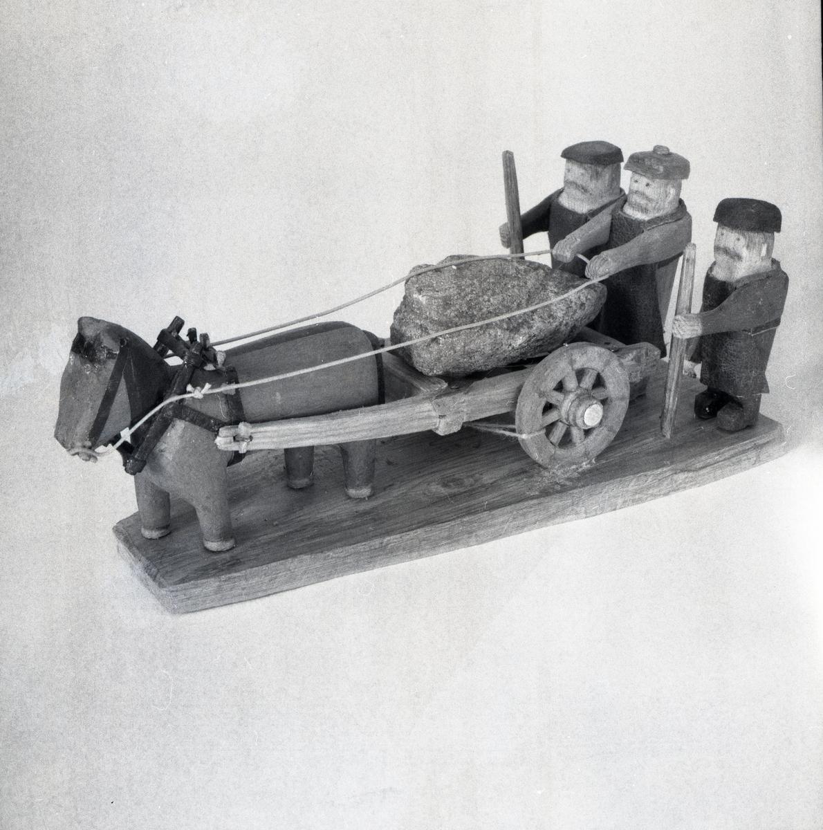 En modell föreställande tre figurer och en häst med vagn i trä.