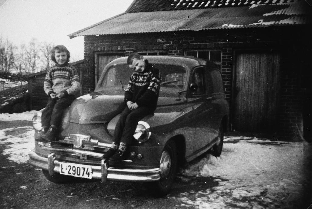 """Tvillingane Bjarne Kalberg (1.12.1951 - ) og Margrete Kalberg (1.12.1951 - ) sit på """"gamle Standarden"""" i gardsrommet."""