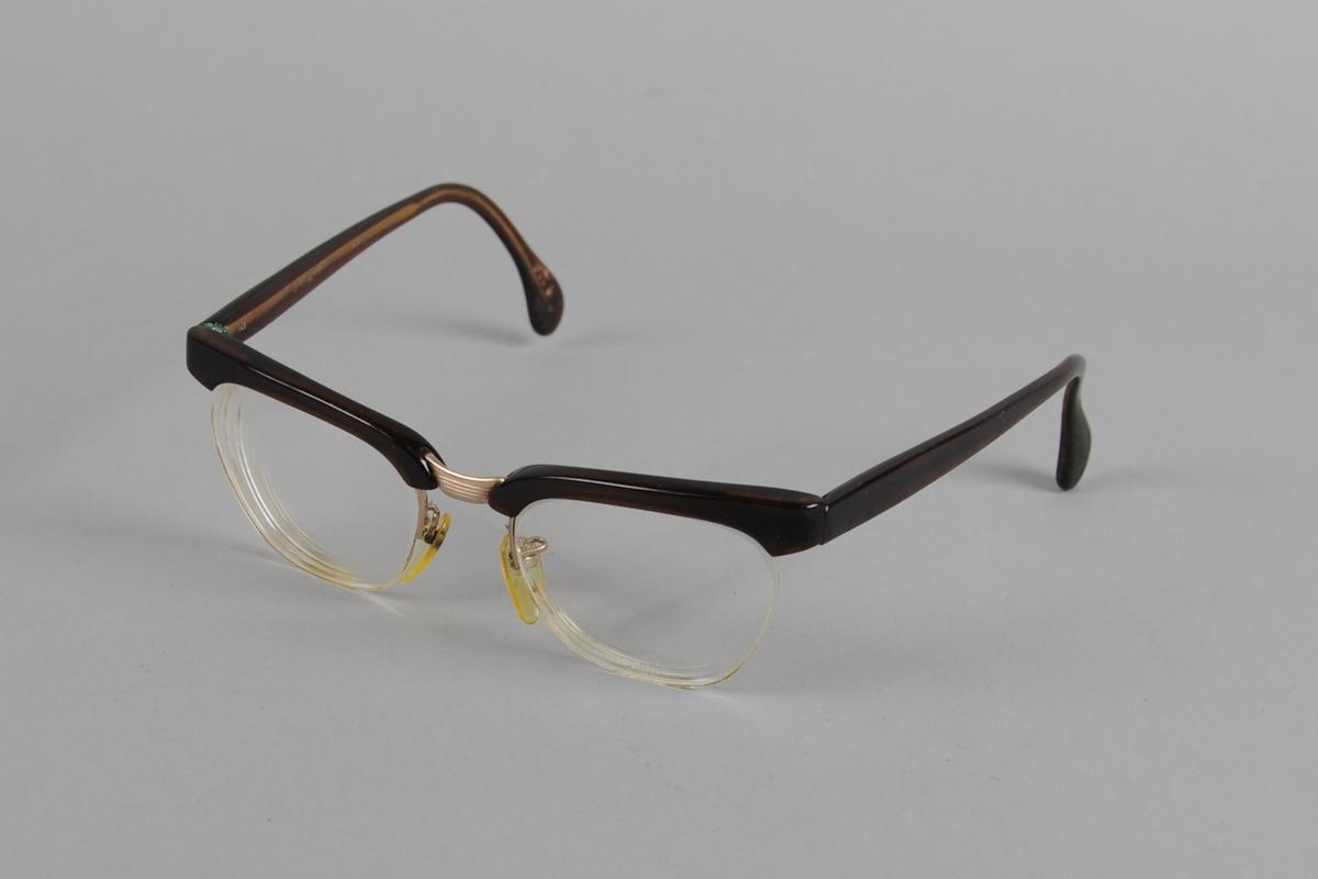 Briller med brilleinnfatning kun på oversiden av brilleglassene. Innfatningen er av metall med mørkebrunt plastbelegg.