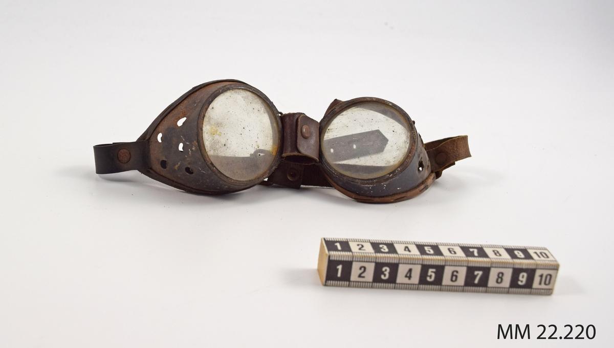 Skyddsglasögon, metallbåge med fem hål i vardera sida förluftcirkulation. Rem av läder och plast för fastsättning runt huvudet.