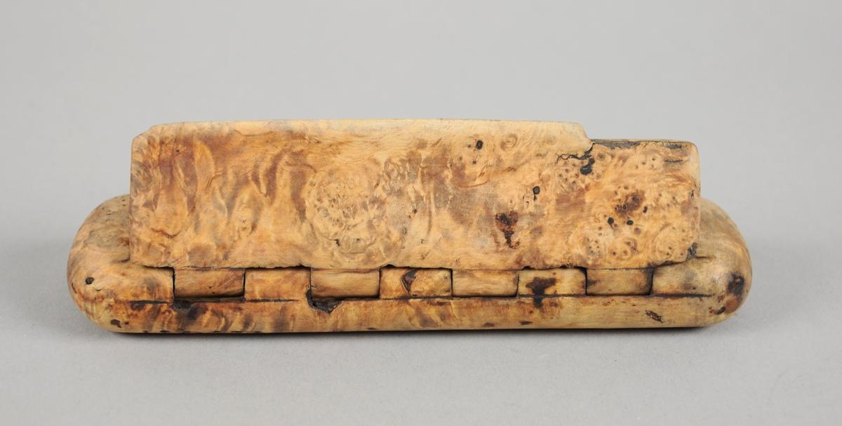 Rektangulært etui av valbjørk med avrundede kanter. Etuiet er uthulet og det er skåret ut hengsler for å feste lokket til etuiet.