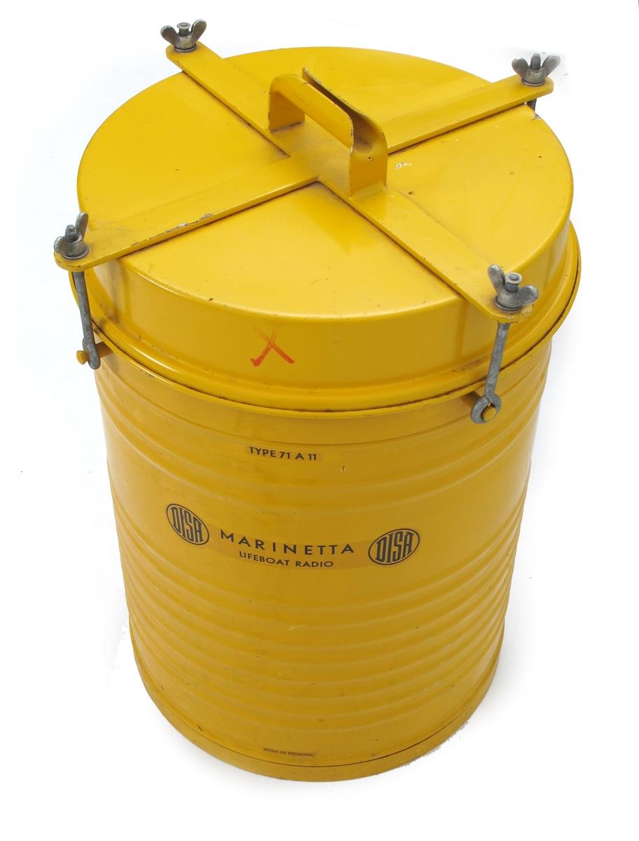 Radiosender pakket i solid emballasje, beregnet for lagring i livbåter. Gulfarget tønneformet beholder med lokk festet med fire vingemuttere.