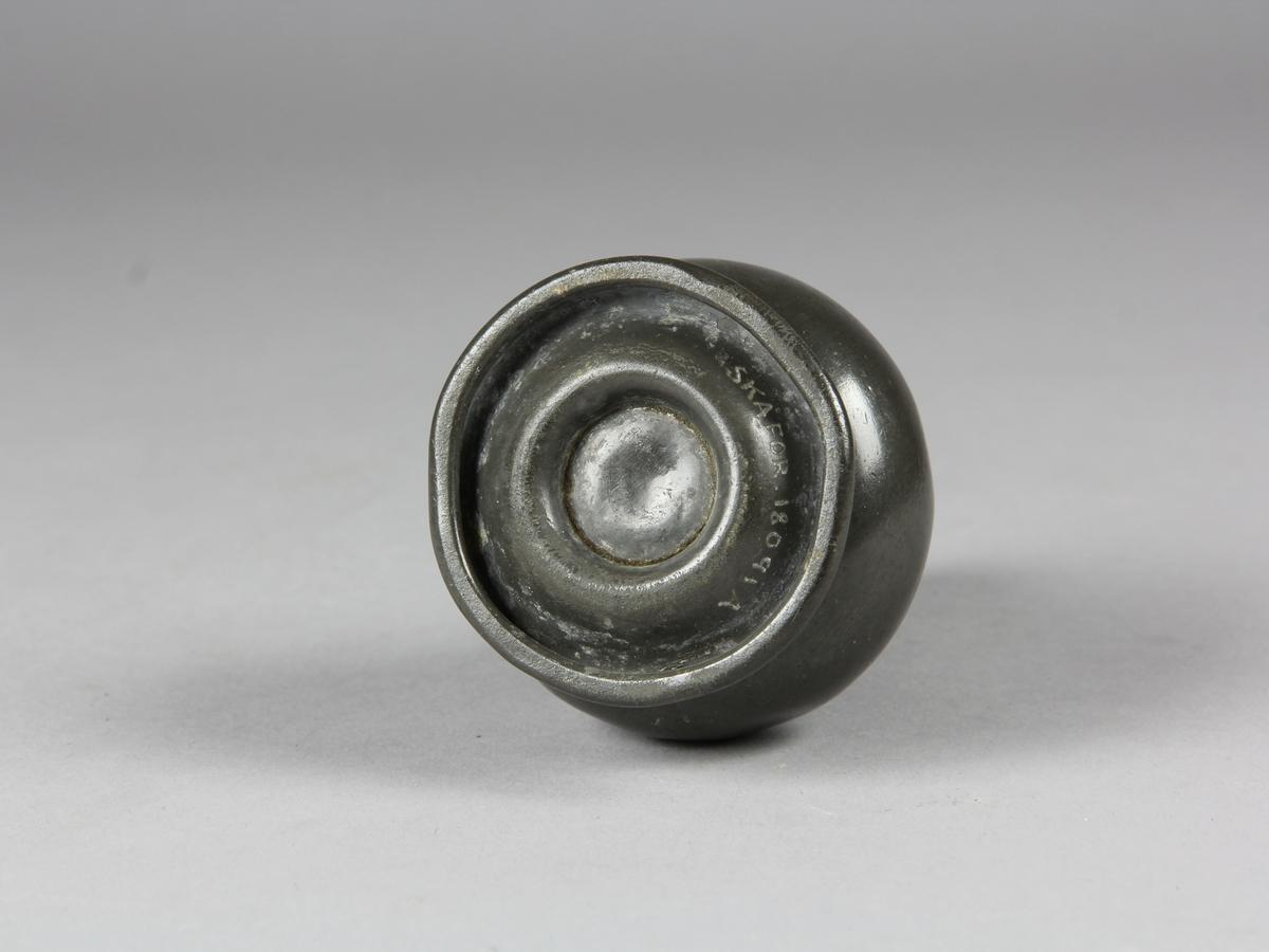 Ströare av tenn. Balusterformad kropp, upptill genombrutet lock som är krönt med en knopp. Nedtill rund fotplatta.