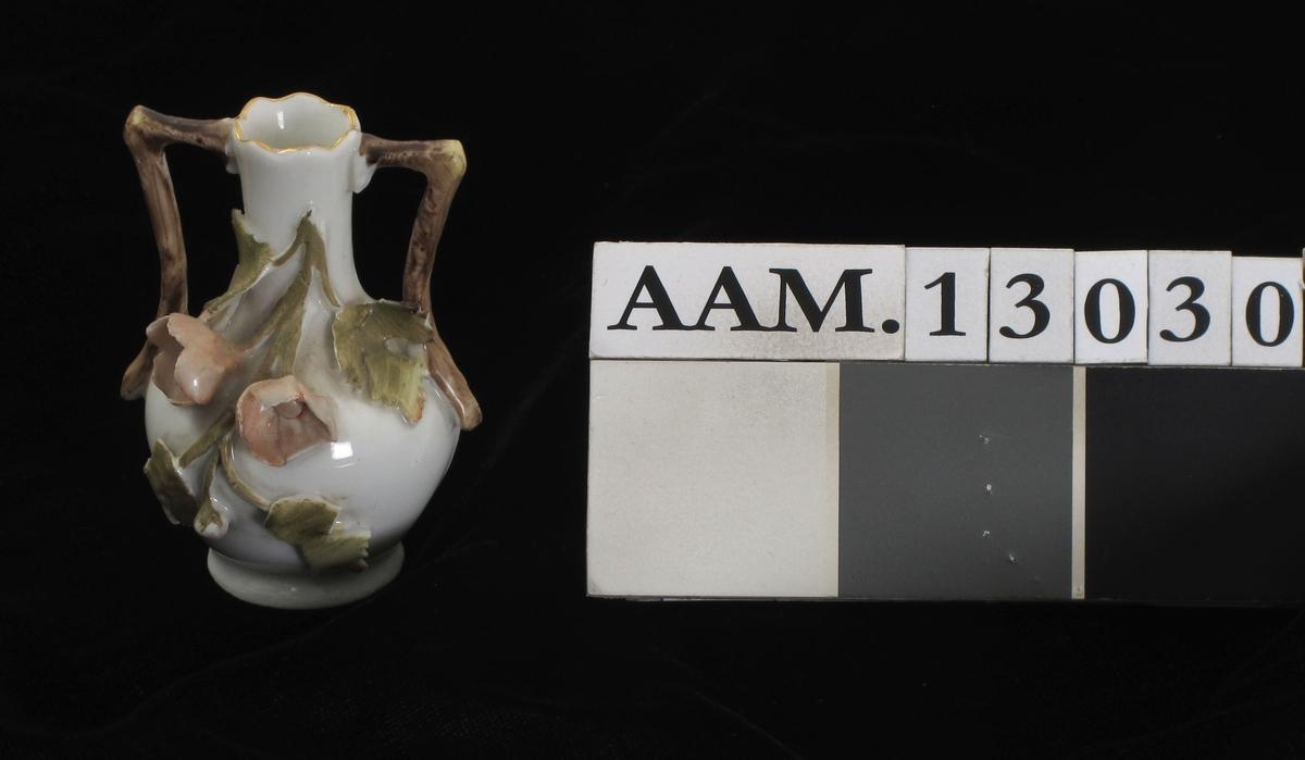 Liten kuleformet vase med lav stett og smal høy hals. To vinkelrette brune hanker. På den ene side av korpus to rosa blomster på en blekgrønn gren, pålagt. Ustemplet.