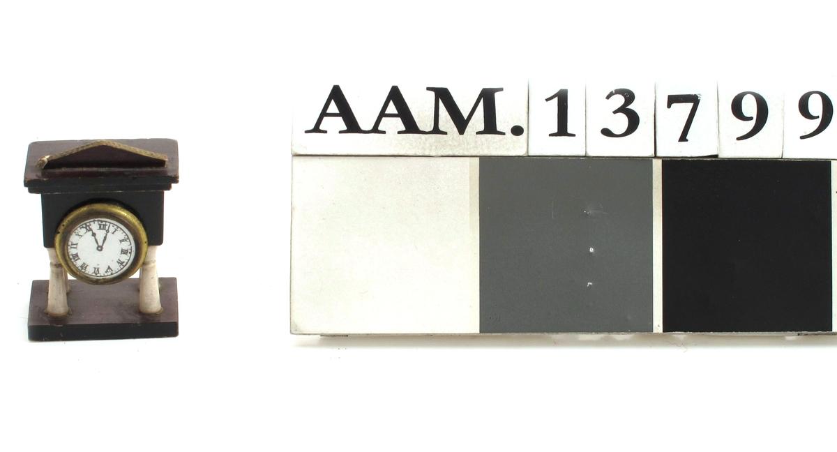 Kaminur, mørkebrunt tre med 4 hvite søyler, urskive med romertall, lav gavl.