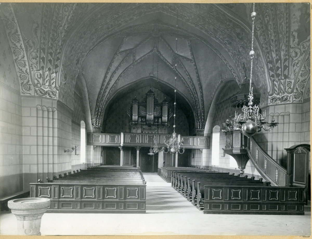 Dingtuna sn, kyrkan.  Interiör mot väster, med foten till dopfunten i förgrunden, kyrkbänkar, malmkrona och med orgelläktaren i bakgrunden.