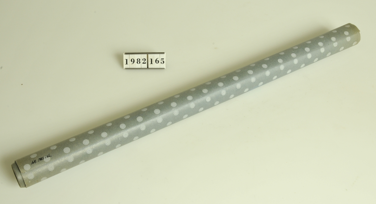 Mönstrat med vita prickar mot blågrå botten.  Hyllpappret funnet i källaren till fastigheten kv. Cederberg 3 (f.d. Andréns tobaksaffär.)