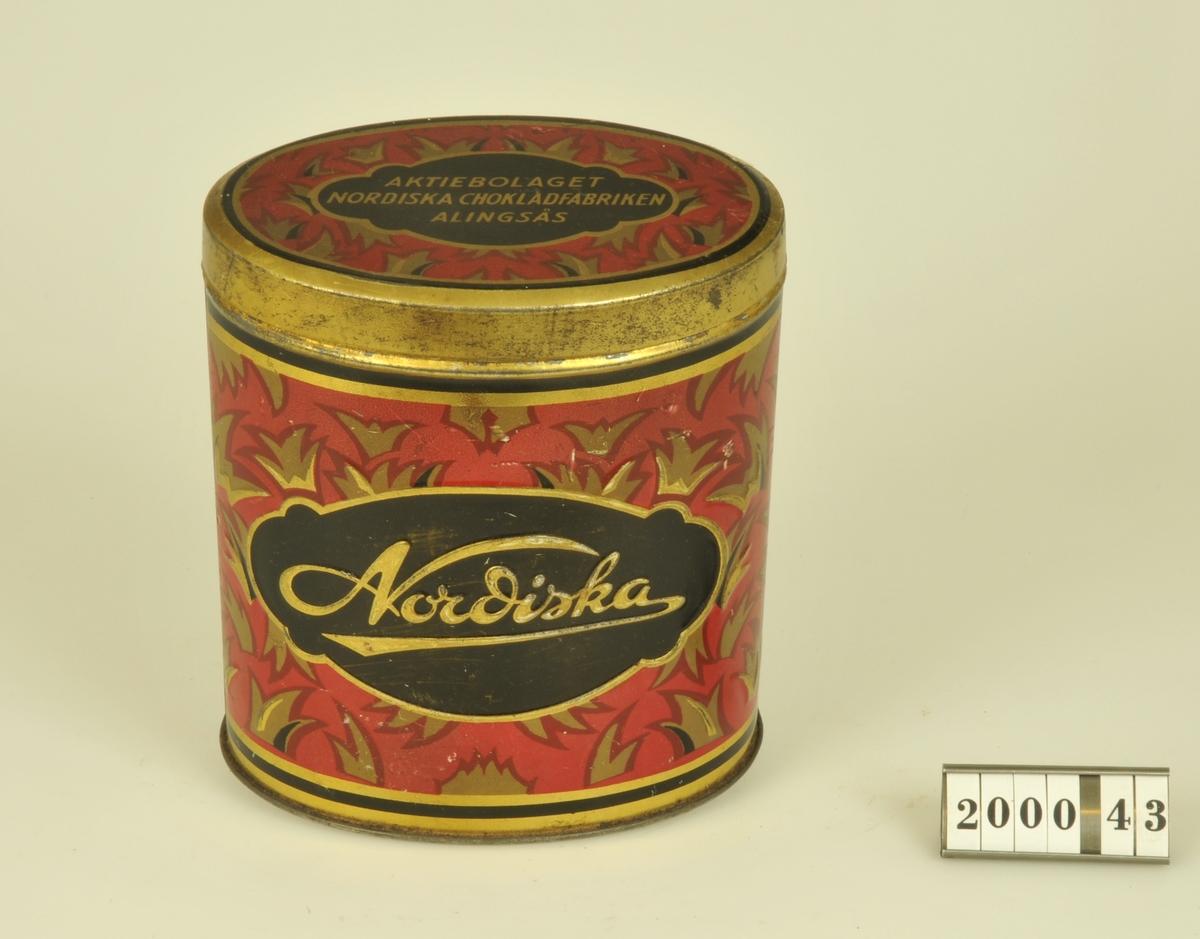 Oval form.  Lackerad i rött, guld och svart.  Burken är tillverkad av firma AB Hugo Brusewitz Bleckvarufabrik, Göteborg.