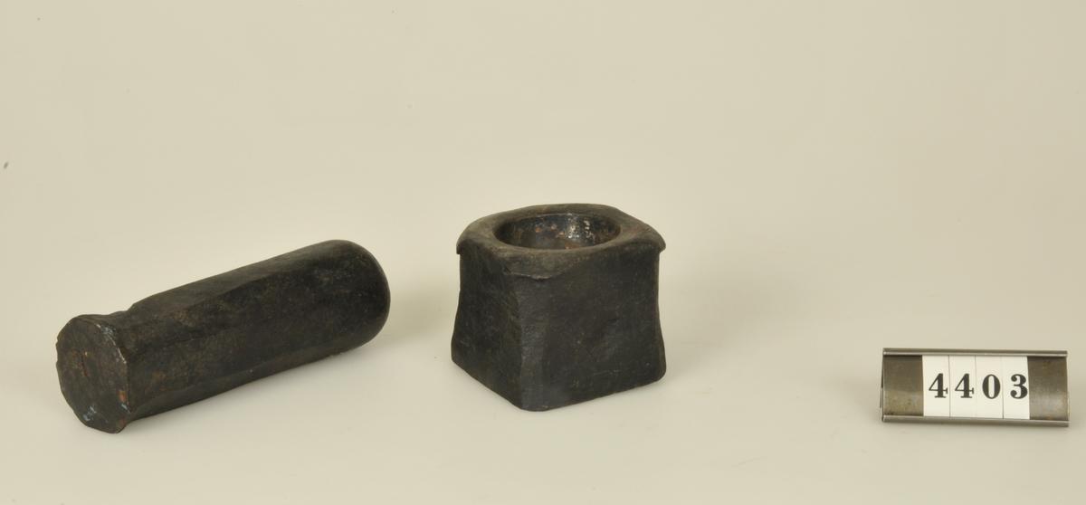 Med stöt. Morteln kubisk med grund skål. Stötens längd 11 cm.