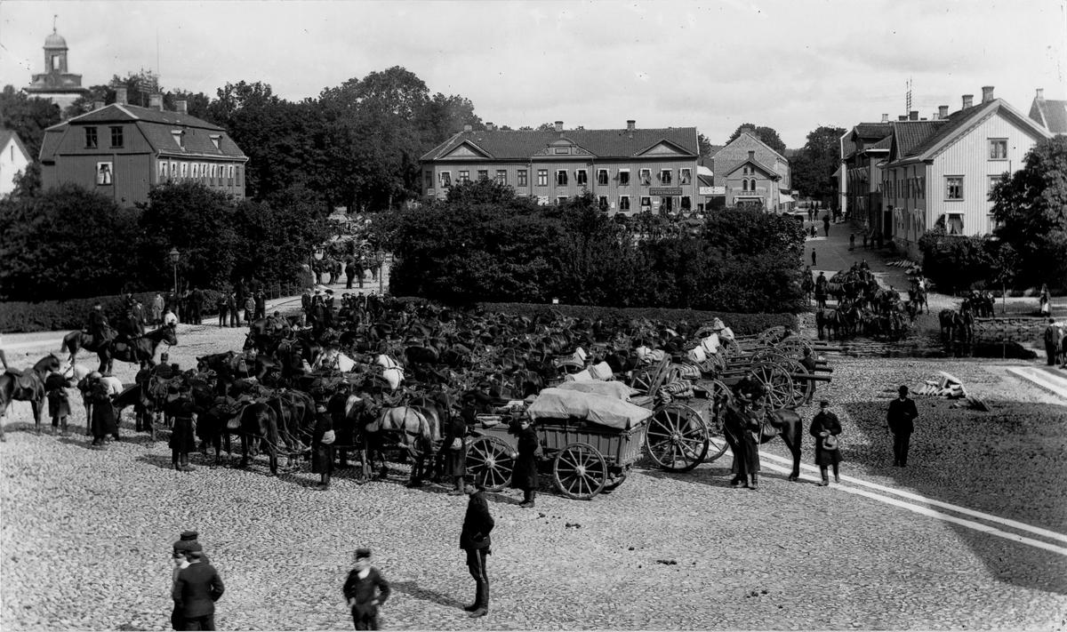 Kungliga Första Göta artilleriregemente rastar på Lilla Torget på marsch till Tåga hed, sommaren 1900. I bakgrunden syns Stora torget.