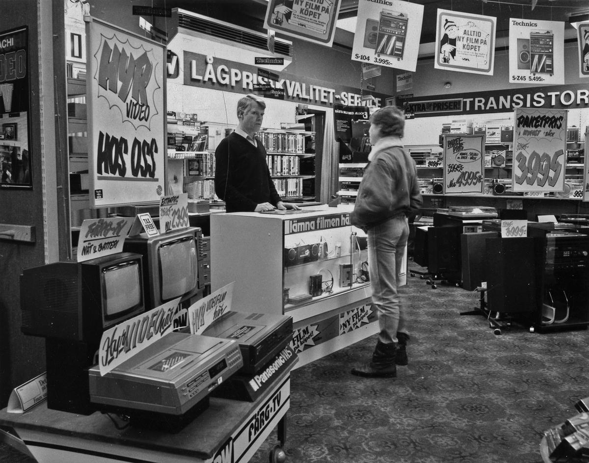 Interiörbild från butiken BW Radio-tv AB där en man expedierar en kund vid disken. Radio, videobandspelare och tv-apparater syns i förgrunden. I taket hänger skyltar med erbjudanden. Kvarteret Gustav 2. Stora Torget.