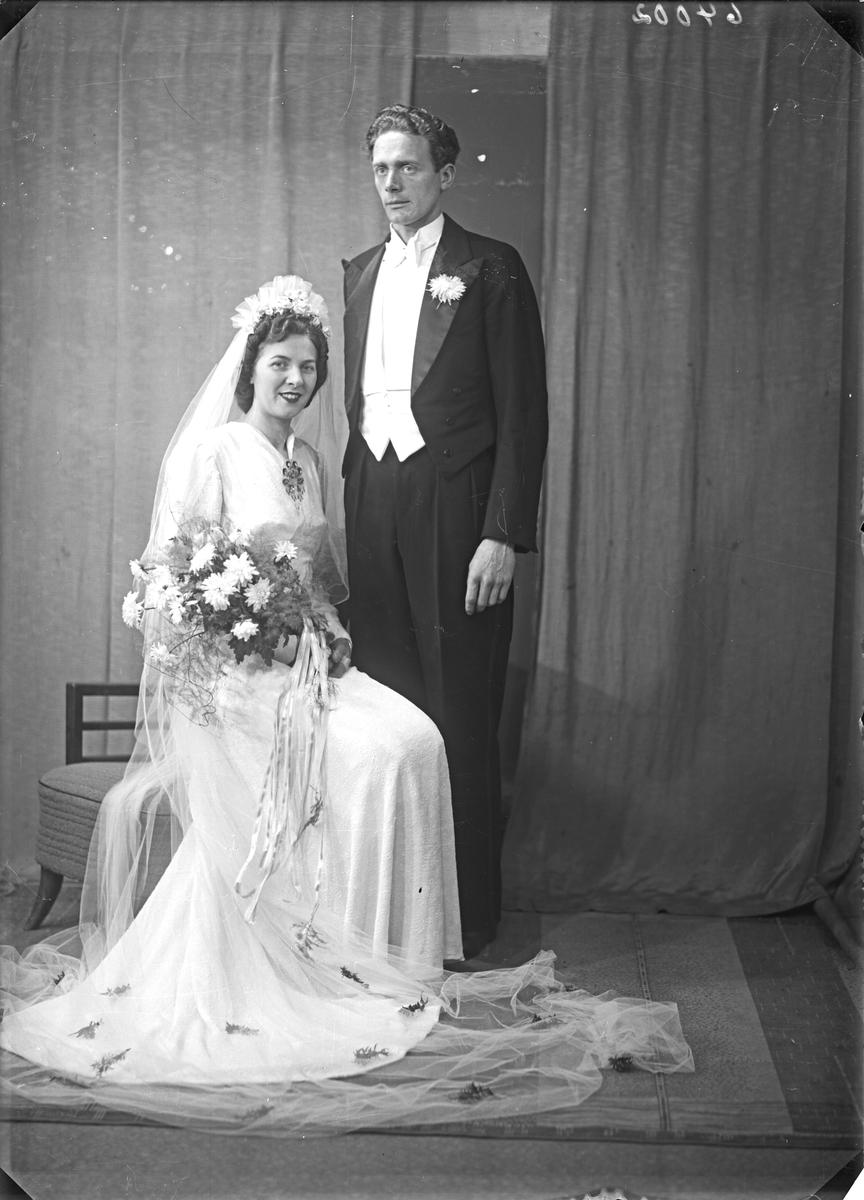 Portrett. Brudebilde. Ung kvinne i hvit brudekjole med slør og ung mann med mørk dress. Brudepar. Bestilt av Audun Kvale. Hordalandsgt.