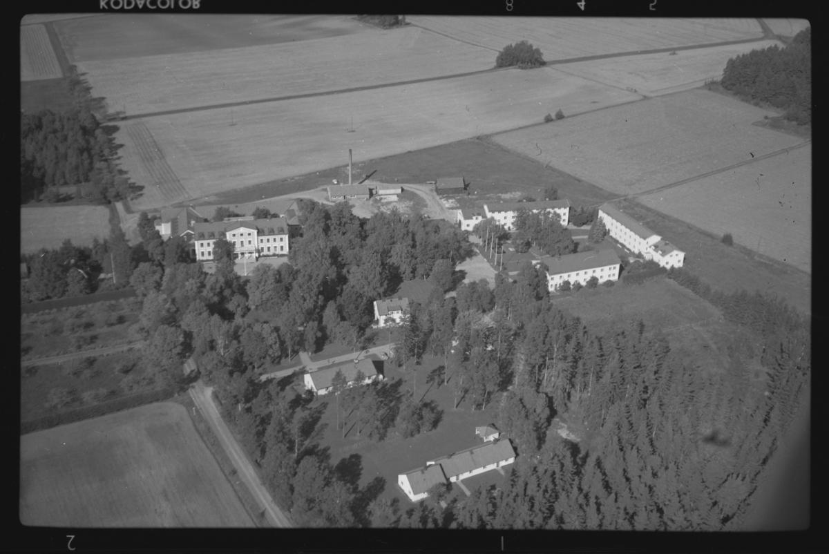 Flygfoto över Tärna Folkhögskola, Kumla kyrkby. Tagen 1963 av AB Flygtrafik Dals Långed.
