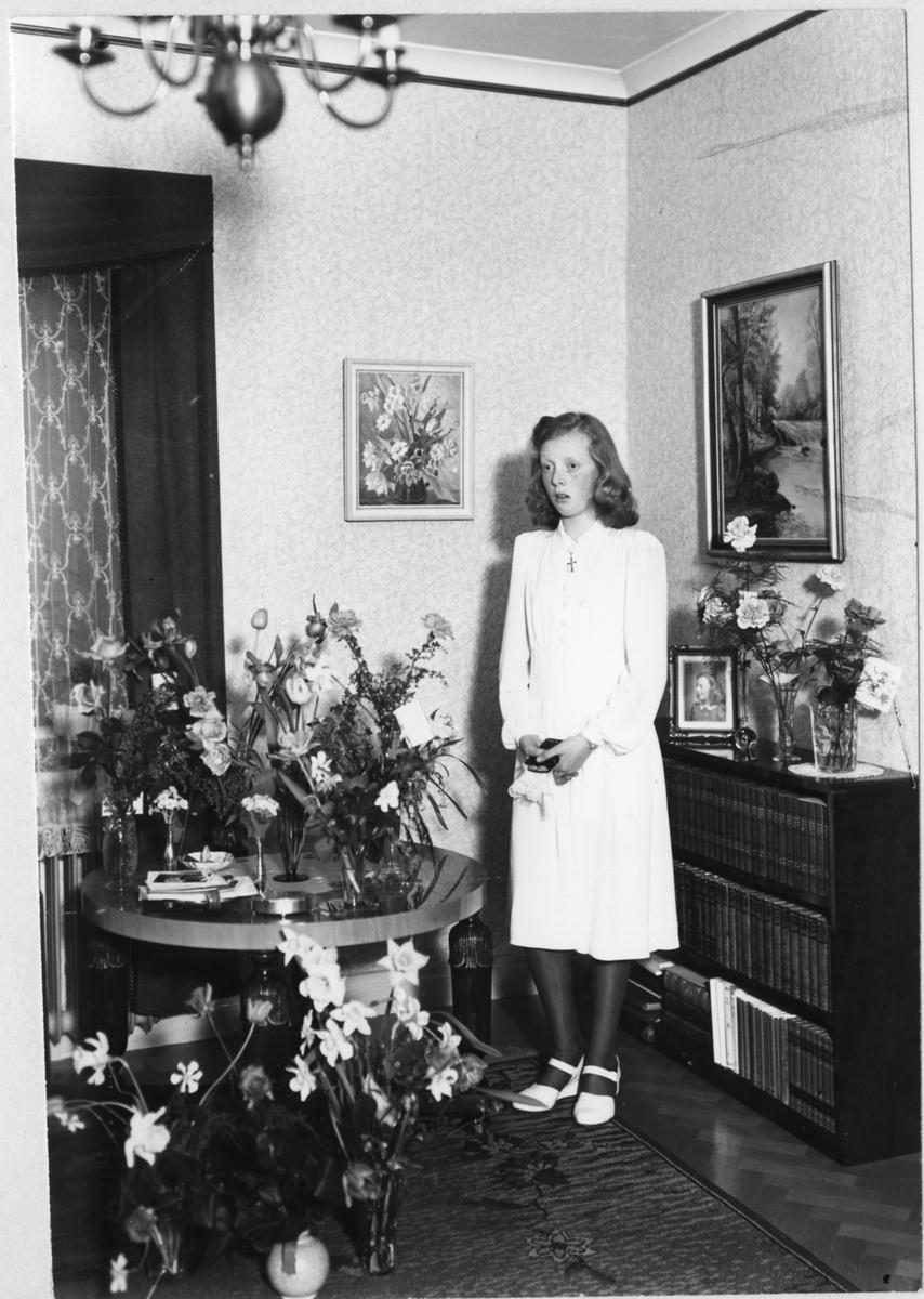En tonårsflicka, Britt Håkansson, fotograferad med en bibel i hand framför ett bord fyllt av blommor efter sin konfirmation.
