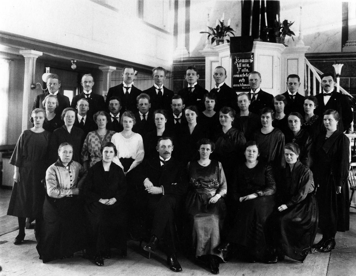 Gruppbild på 34 kvinnor och män i missionskyrkans kyrksal, stående och sittande, framför kyrkans predikstol. Under antependiet en tavla med ett bibelcitat.