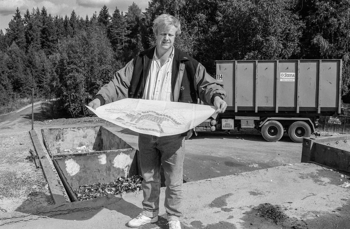 Follo Truckutleie på Langhus, eier Bjørn Prytz holder en plantegning. Truck og gravemaskin.