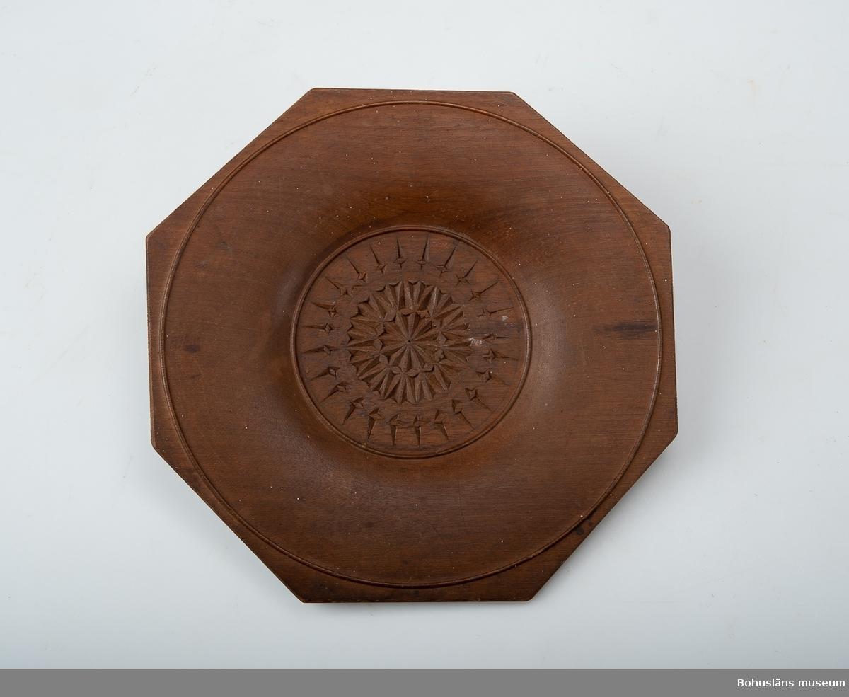 Ur handskrivna katalogen 1957-1958: Trätallrik, flat. Mått c:a 21,5 x 21 cm. Bottendiamet.: c:a 10 cm. Åttakantig. Utskuret mönster i botten. Hel.  Lappkatalog: 66