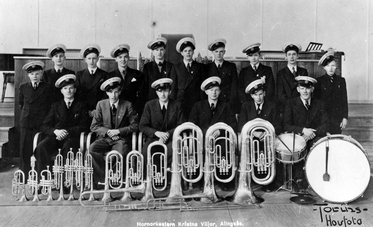 Gruppbild med 16 pojkar och män klädda i uniform från Missionkyrkans hornorkester - Kristna Viljor. Framför sig har de ställs sina musikinstrument i storleksordning.