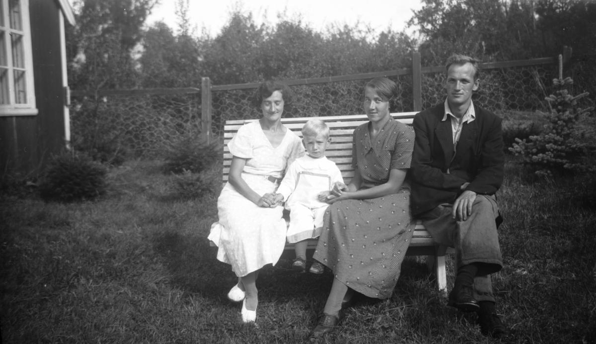 Fire personer på en benk ute.