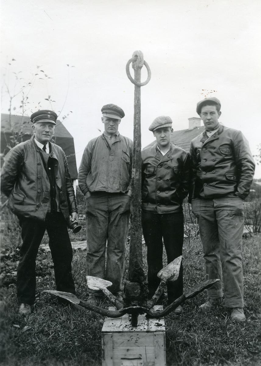 Kolbäck sn. Ankare funnet i Kolbäcksån, 100 meter norr om bron. Fyra män står bakom ankaret.