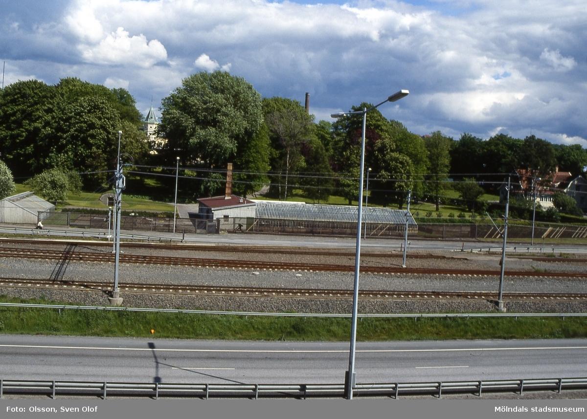 Vy över Kungsbackaleden, järnvägen och Nämndemansgatan mot Papyrus växthus i Forsåker, Mölndal, i maj 1990. Mellan träden i parken skymtas även Villa Papyrus.