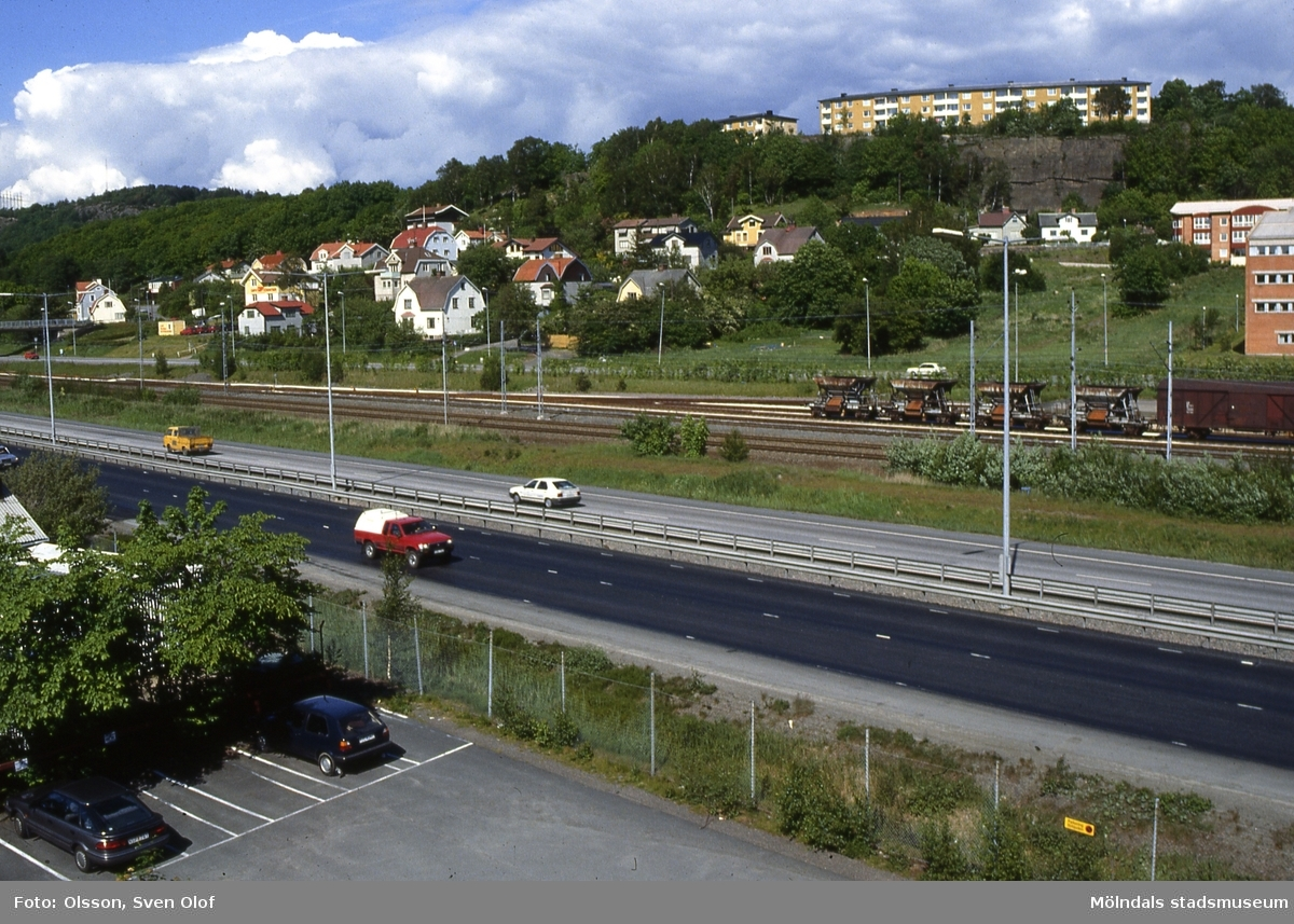 Vy från Platzers hus vid Ågatan över Kungsbackaleden och järnvägen mot bebyggelse i Trädgården, Mölndal, i maj 1990. Uppe på höjden ses även bostadsbebyggelse i Enerbacken. D 10:36.