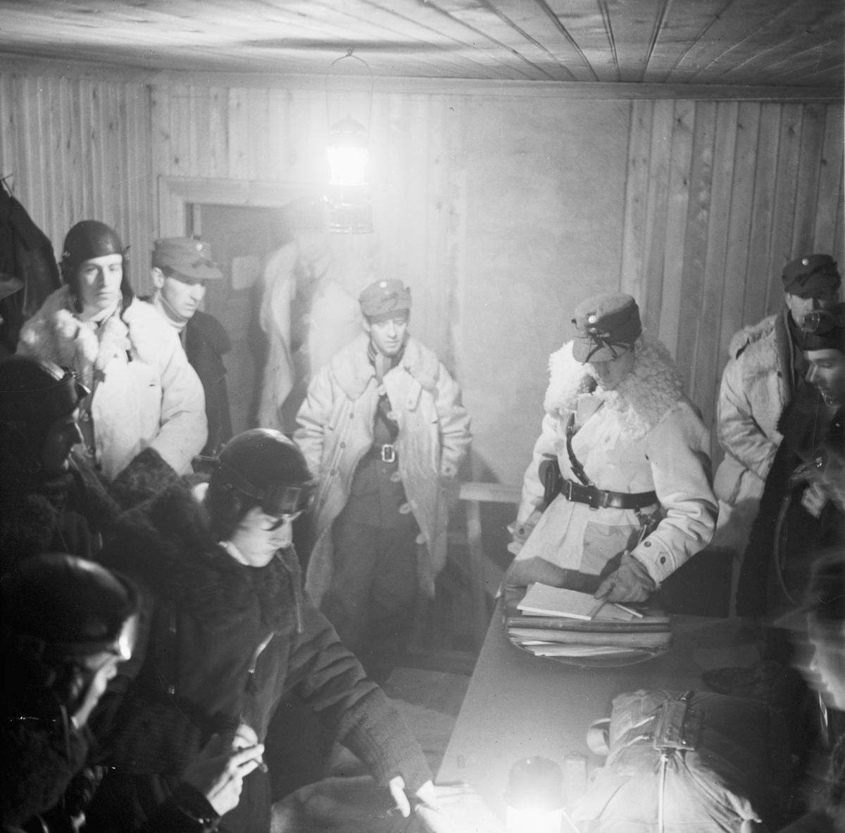 Ordergenomgång inne på förläggning vid Svenska frivilligkåren i Finland, F 19. Militärer klädda i vinteruniform och flygdräkt.