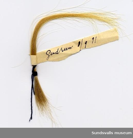 Blond hårlock i snodd. På en lapp står det skrivet: Blont hår tillhör Marit 1/9 91