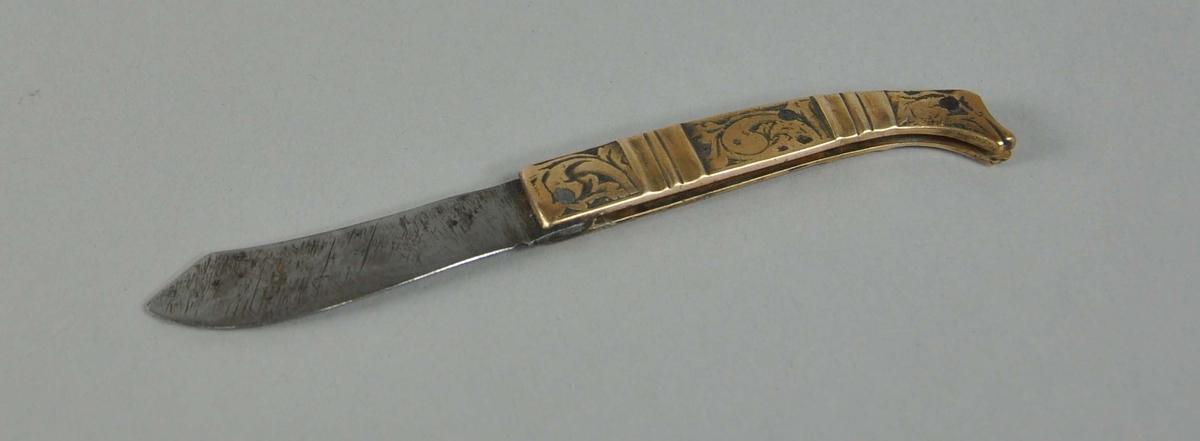 Foldekniv med hank av messing. Hanken har akantuslignende graveringer og profilerte tverrsnitt. Hanken er avrundet i enden.