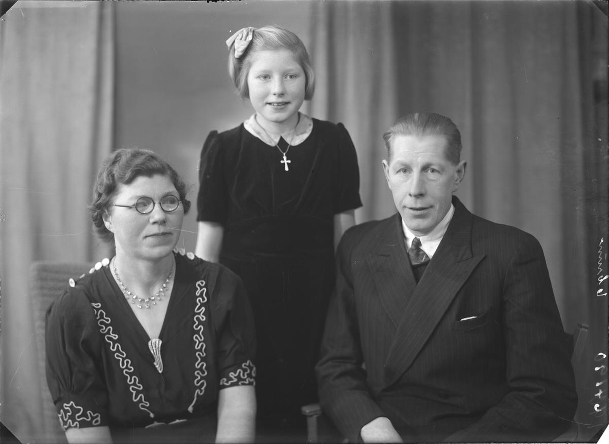 Gruppebilde. Familiegruppe på tre.  Mørkhåret kvinne med runde briller i mørk kjole med lyse broderinger i front,  ung lyshåret pike i mørk kjole med lys krage og mørkhåret mann i mørk stripet dress, hvit skjorte og slips. Bestilt av Thorvald Salvesen. Karøygt. 90