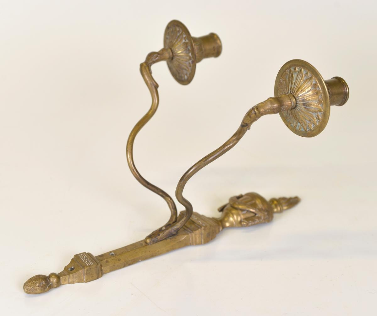 Med två armar.  Av säljaren inköpt på en bondgård nära Gräfsnäs. Det uppgavs där att lampetten ursprungligen tillhört inventarierna på Gräfsnäs slott.  Modell/Fabrikat/typ: Rokoko
