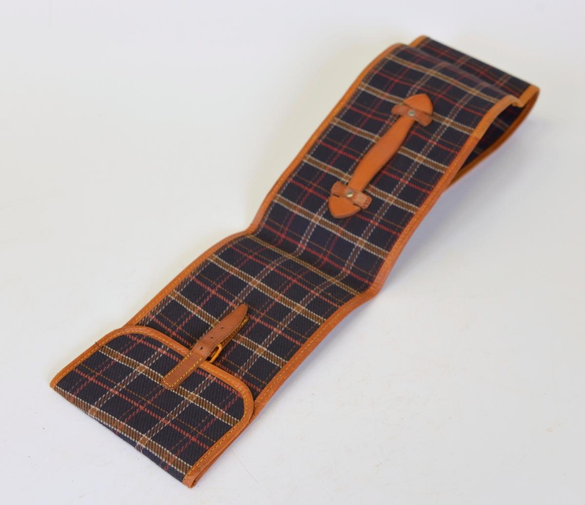 Fodral till golfklubbor. Av rutigt tyg i blått, brunt, rött och vitt. Detaljer i läder.