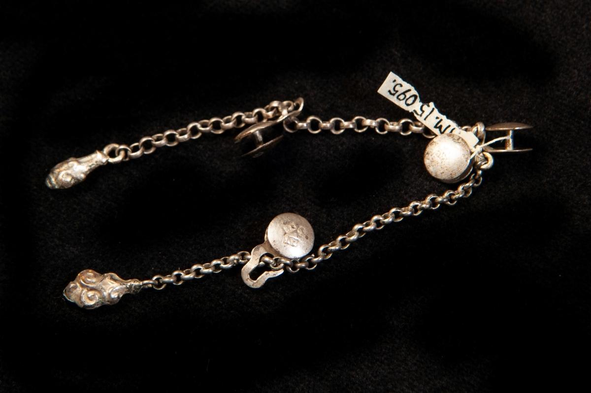 En enkel kedja av silver med fyrast. små, runda s.k. dubbelknappar. Kedjan avslutad med ovala små gjutna klumparmed enkel pressad dekor.Något otydliga stämplar (på knapparna).
