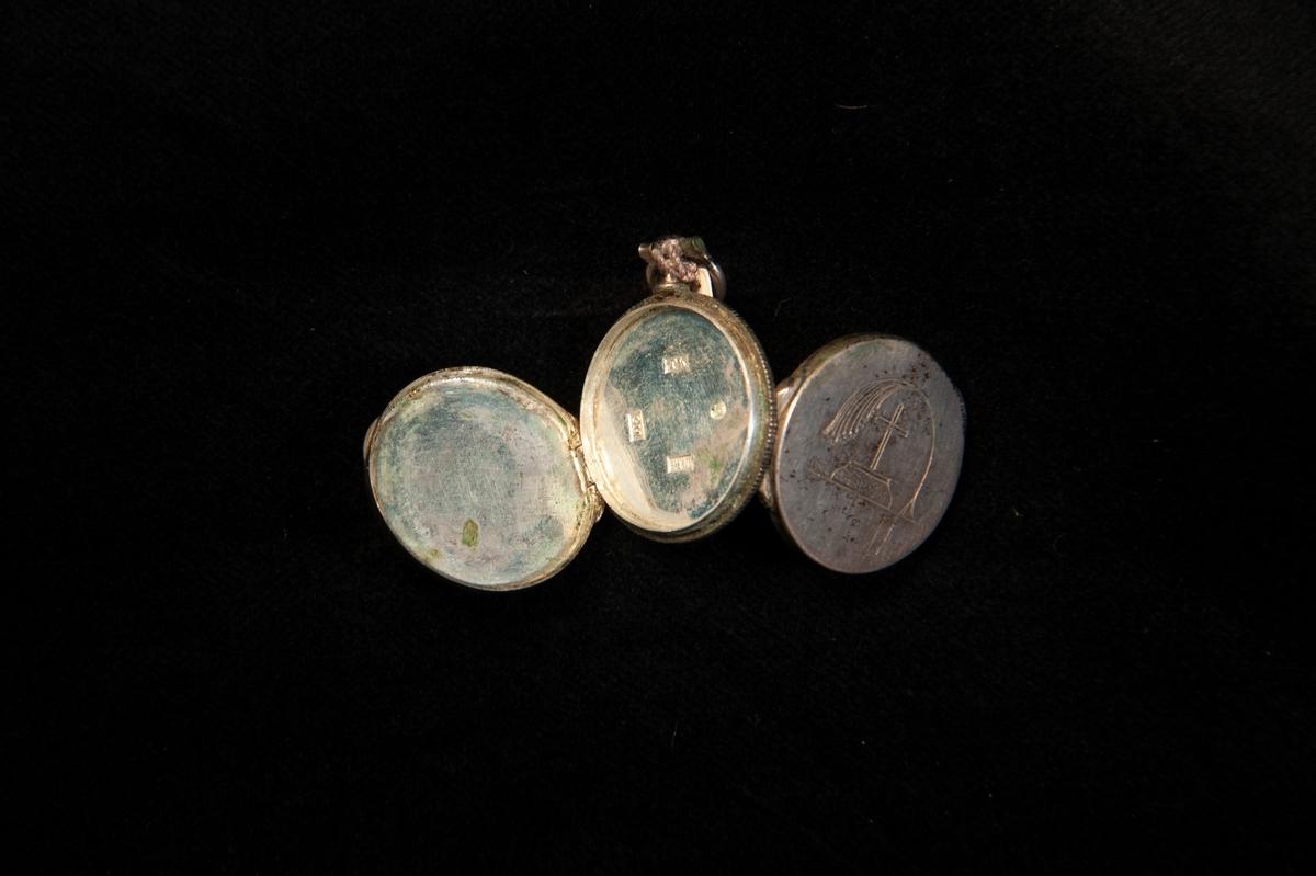 """En rund medaljong av silver som går att öppna på både fram och baksida. Framtill graverat: """"Minne"""", omgivet av snirklig bård. Baktill graverat en palmkvist lutad över ett kors. Stämplad invändigt."""