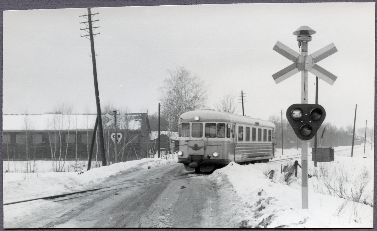 Rälsbuss passerar järnvägsövergång i Vena.