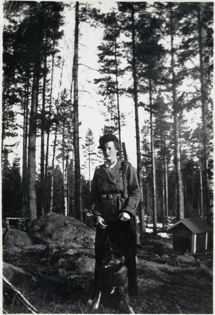 Siri Andersson med hund och gevär.