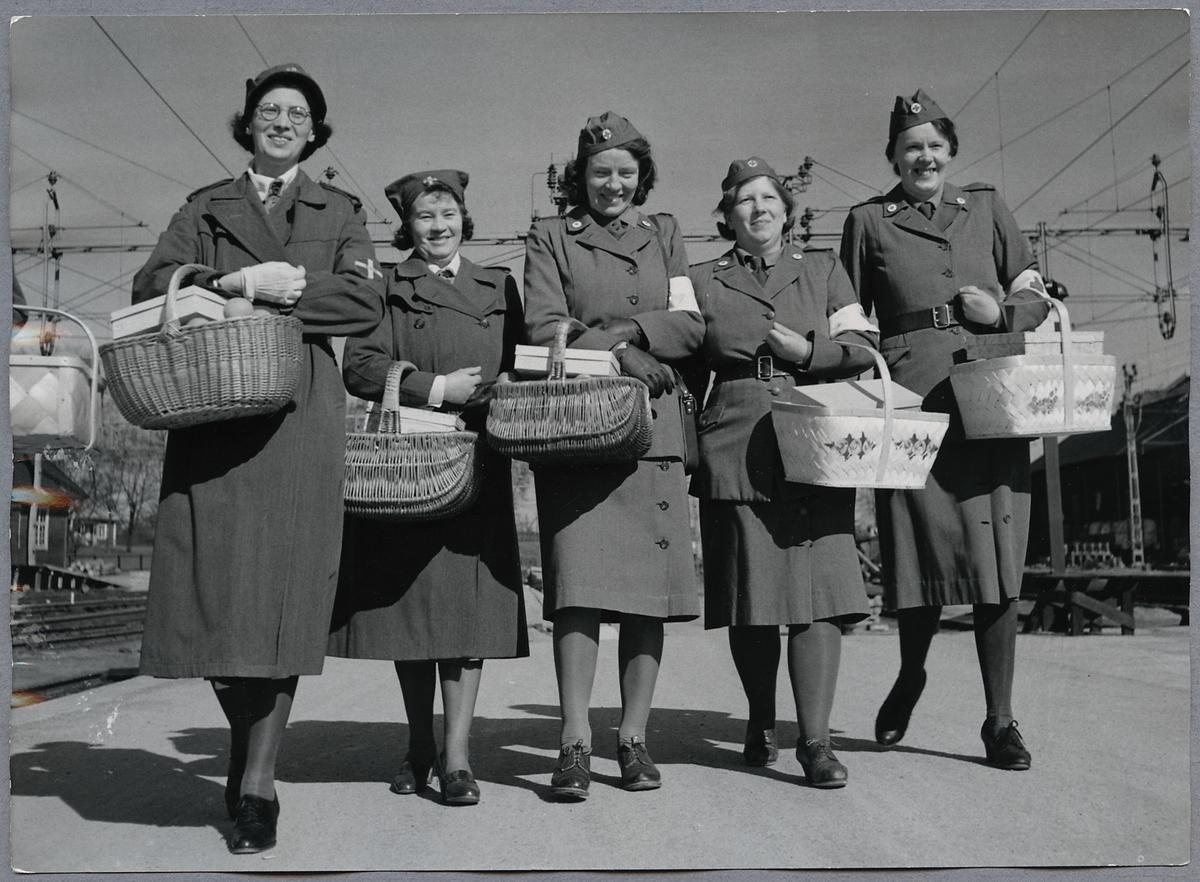 Röda Korssystrar samt personal ur Lottakåren är redo att dela ut förnödenheter till skadade tyska soldater ombord på tyskt sjukvårdståg som ska passera Hallsberg.