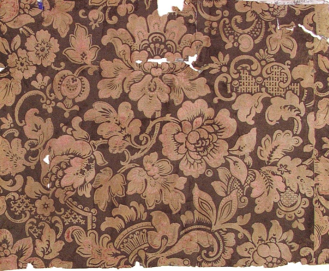 Ett ytfyllande fantasifullt blommönster med rocailler och inläggningar i brunt och något rosa på ofärgat papper.   Tillägg historik:. Tapet från ett hus byggt 1820.