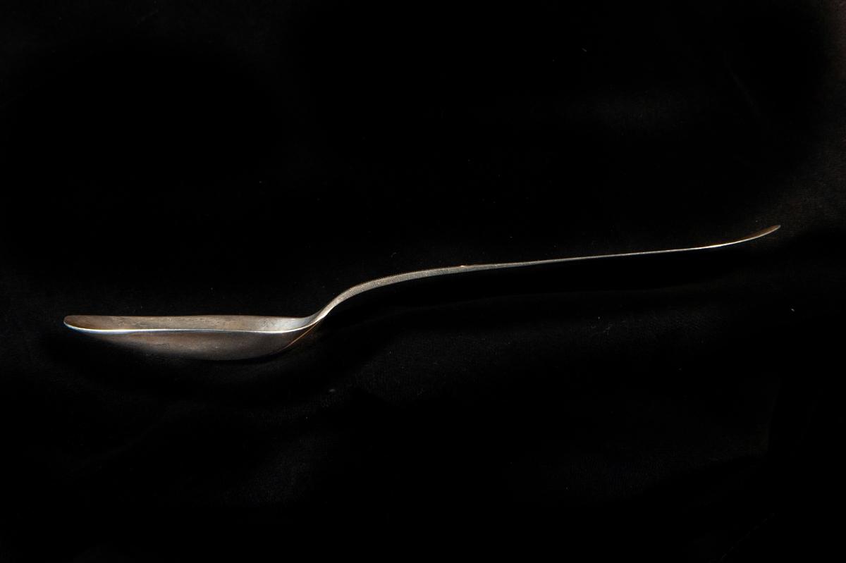 """En matsked av silver. Enkel, spetsig modell. Graverad dekor med punkter m.m. längs kanten på skaftet. Stämplad på ovansidan. På baksidan är ingraverat: """"Elsa"""""""